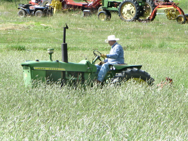 Larry mows Vickers Ranch hay field on John Deer tractor