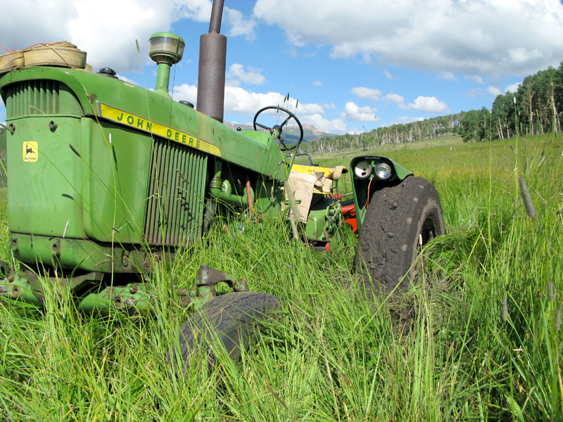 John Deere tractor stuck in the mud while mowing hay