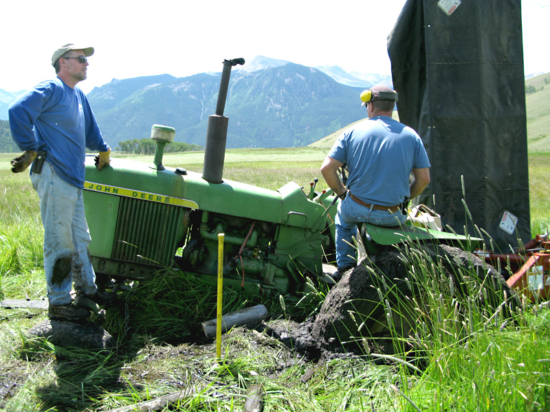 Jim and Paul ponder pulling John Deere tractor out of the mud