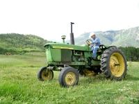 Larry Vickers mows hay on old John Deer tractor