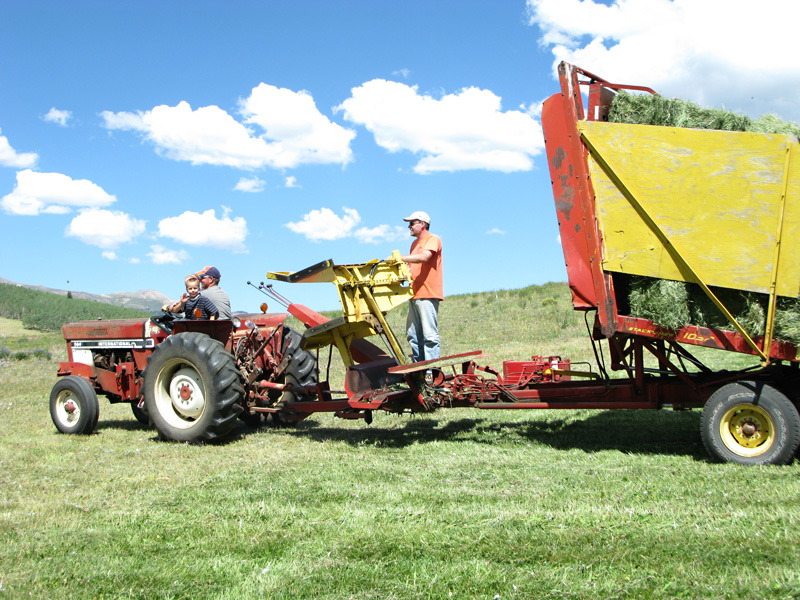 Jim rides the stacker back to the hay barn with a full load
